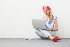 Fashion blogger sitting on the floor and using laptop Royalty Free Stock Images