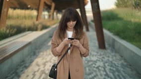 Fashion blogger walking in a park, reading comments to her post and smiling. Young and beautiful fashion blogger with long brown hair wearing beige coat and bag stock video
