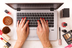 Fashion blogger working at office desk with a laptop: fashion, beauty and technology concept Royalty Free Stock Images