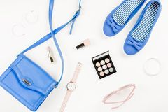 Fashion blogger workspace flat lay with navy flats, cosmetics, purse, sunglasses. Top view stock photo