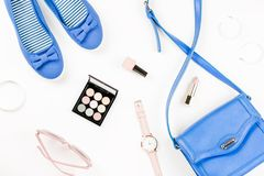 Fashion blogger workspace flat lay with navy flats, cosmetics, purse, sunglasses. Top view stock images