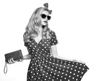 Fashion Blond Girl in Polka Dots Dress. Outfit. Fashion Model Girl in Polka Dots Summer Dress. Stylish Curly hairstyle, Trendy Clutch, fashion Headband stock image