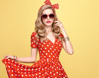 Fashion Blond Girl in Red Polka Dots Dress. Outfit. Fashion Model Girl in Polka Dots Summer Dress. Stylish Curly hairstyle, Trendy Clutch, fashion Red Headband royalty free stock photography
