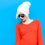 Fashion blond girl with trendy cap and sunglasses on a blue back Royalty Free Stock Images