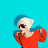Fashion blond girl with trendy hat and sunglasses on a blue back Royalty Free Stock Images