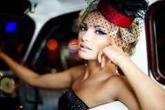 Fashion blond model in retro style in old car Stock Photography