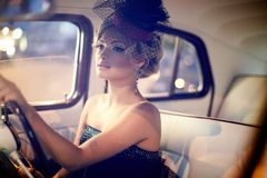 Fashion blond model in retro style in old car Royalty Free Stock Image