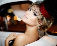 Fashion blond model in retro style in old car Royalty Free Stock Photography