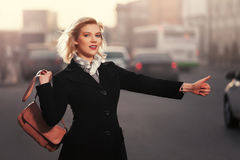 Fashion blond woman in black coat hailing a taxi cab walking in city street. Happy fashion blond woman in black coat hailing a taxi cab walking in city street Royalty Free Stock Image