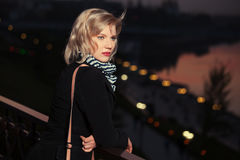 Fashion blond woman in black coat in a night city street Stock Images