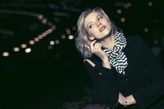 Fashion blond woman in black coat in a night city street. Happy young fashion blond woman in black coat in a night city street Royalty Free Stock Photography
