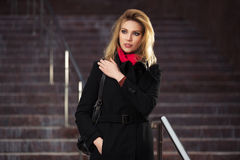 Fashion blond woman in black coat on the steps Royalty Free Stock Photos