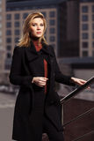 Fashion blond woman in black coat walking on city street. Fashion blond woman in black coat walking on the city street Royalty Free Stock Photo