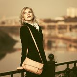Fashion blond woman in black coat walking in city street Royalty Free Stock Photos