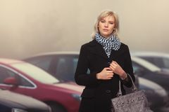 Fashion blond woman in black coat walking in a city street Stock Images