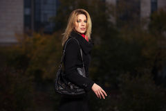 Fashion blond woman in black coat walking on night city street. Fashion blond woman in black coat with handbag walking on night city street Royalty Free Stock Photo