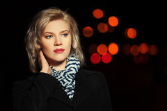 Fashion blond woman in black coat walking in a night city street Stock Images