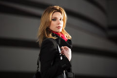 Fashion blond woman in black coat walking on night street Royalty Free Stock Photos