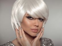 Fashion blond woman with bob short hairstyle and manicure nail p. Olish. Close up portrait of blonde girl model with white hair presenting diamond ring on finger stock image