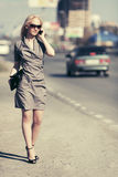 Fashion blond woman calling on cell phone on city street Royalty Free Stock Image