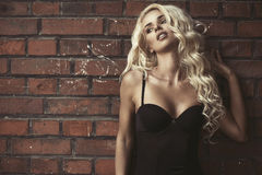 Fashion blond woman over brick wall Royalty Free Stock Photos