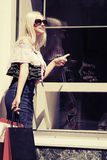 Fashion blond woman with shopping bags at the mall window Stock Photos