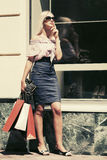 Fashion blond woman in sunglasses with shopping bags Stock Photo