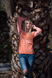 Fashion blond woman wear long sleeves blouse and jean leaning on a tree Stock Photography
