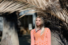 Fashion blond woman wear long sleeves blouse and jean leaning on a tree Stock Image