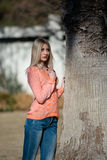 Fashion blond woman wear long sleeves blouse and jean leaning on a tree Royalty Free Stock Photography