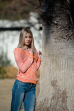 Fashion blond woman wear long sleeves blouse and jean leaning on a tree Stock Photo
