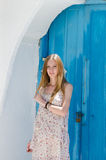 Fashion blonde against the blue door in Mykonos island Royalty Free Stock Images