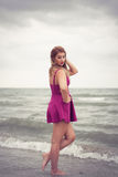 Fashion blonde at the beach sea side posing shoe-less in water Royalty Free Stock Photos
