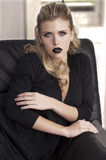 Fashion blonde on a black sofa Royalty Free Stock Photos
