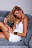 Fashion blonde girl looking at camera. Sensual fashion female model in white dress lying on the sofa Royalty Free Stock Photos