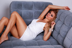 Fashion blonde girl lying on a sofa. Sensual fashion female model in white dress lying on the sofa Stock Images