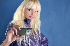 Fashion blonde girl photo camera mobile phone. Blue royalty free stock photo