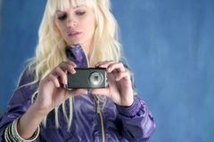 Fashion blonde girl photo camera mobile phone. Blue royalty free stock image