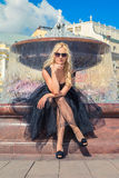 Fashion Blonde Girl Sitting on Bench Near Fountain. Street Fashi. On. Urban Lifestyle. Young Beautiful Woman Walking Outdoor Stock Image