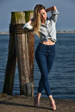 Fashion blonde model posing on the pier against the water. Royalty Free Stock Images