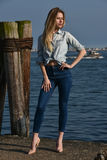 Fashion blonde model posing on the pier against the water. Stock Photo