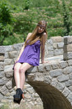 Fashion blonde with short dress sitting on small stone bridge Stock Photography