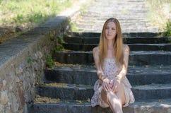 Fashion blonde wearing flower dress sitting on stone stairs Stock Image