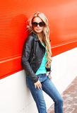 Fashion blonde woman in black rock jacket sunglasses at city over red stock photos