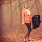 Fashion blonde woman with jacket in autumn park. Royalty Free Stock Image