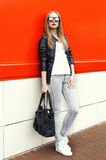Fashion blonde woman wearing a rock black leather jacket, sunglasses and bag over red Royalty Free Stock Image
