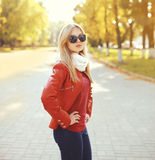 Fashion blonde woman wearing a sunglasses and red leather jacket. With scarf in autumn park Royalty Free Stock Photos