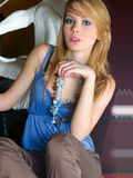 Fashion blondie. Young beautiful woman in trendy outfit, holding her necklace Royalty Free Stock Photos