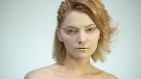 Fashion body art. Woman with golden skin and lips. Model girl face portrait. Glamour shiny professional makeup. Gold. Paint smudges drips from woman face, lips stock video