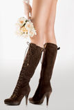 Fashion boots and long legs. A closeup view of high fashioned leather boots worn by a sexy woman with long legs and holding a bouquet of roses Royalty Free Stock Photos